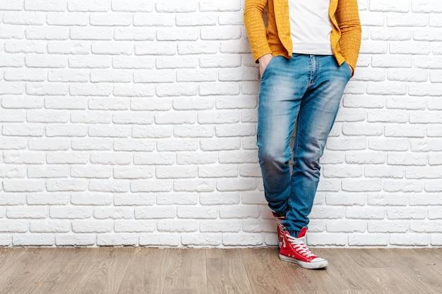 Moda młody mężczyzna nogi w dżinsy i trampki na drewnianej podłodze