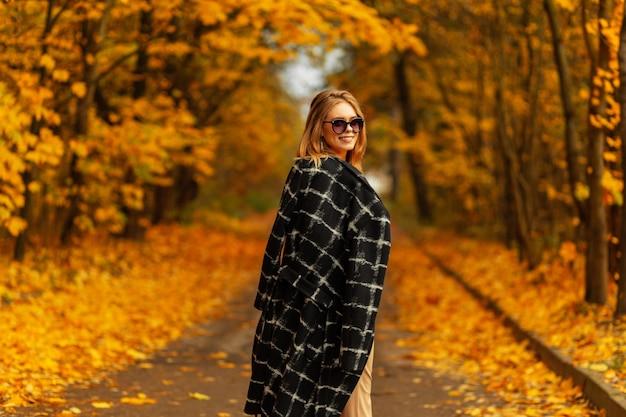 Moda model młoda kobieta w słomkowym kapeluszu w pasiastą koszulę w beżowe spodnie w sandałach na obcasie pozuje w pobliżu czarnego budynku w słoneczny dzień. europejski modna dziewczyna na zewnątrz. nowa kolekcja stylowych ubrań dla kobiet
