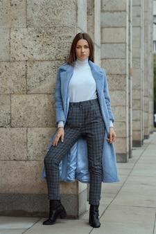 Moda modelki brunetka kobieta w rozpiętym niebieskim płaszczu z białą kurtką i szarymi kraciastymi spodniami i czarnymi butami pozuje do kamery stojącej w pobliżu kamiennych kolumn na ulicy