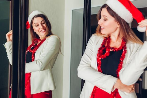 Moda na nowy rok lub przyjęcie świąteczne. kobieta sprawdza strój patrzeje lustro, jest ubranym kapelusz świętego mikołaja