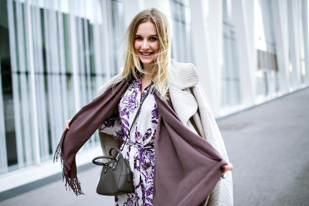 Moda na styl życia portret całkiem eleganckiej kobiety w modnym stylowym stroju, fioletowym długim szaliku, luksusowym płaszczu z kaszmiru i sukience midi, uśmiechnięty koniec cieszący się, pozostań przed nowoczesnym centrum biznesowym