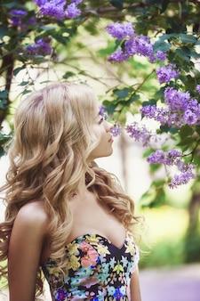 Moda na zewnątrz piękna młoda kobieta w otoczeniu kwiatów bzu latem. wiosna kwiat bzu krzew. portret dziewczyny blondynki