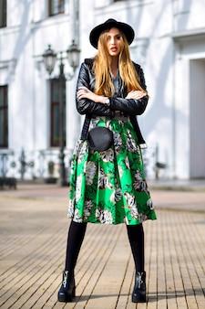 Moda na zewnątrz portret miasta stylowej hipster kobiety spacerującej po ulicy i zabawy, młoda podróżniczka, fashionistka, kobiecy strój piękna, długa spódnica vintage, kapelusz retro i kurtka motocyklowa.