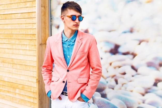 Moda na zewnątrz portret portret młodego stylowego mężczyzny hipster, ubrany w modne klasyczne dorywczo jasne ubrania i okulary przeciwsłoneczne, miękkie pastelowe kolory.
