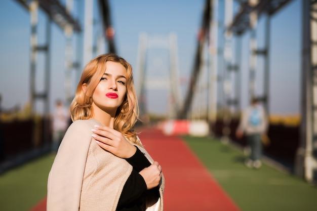 Moda na zewnątrz portret uroczej modelki w jesiennym stroju casualowym spacerującym po mieście