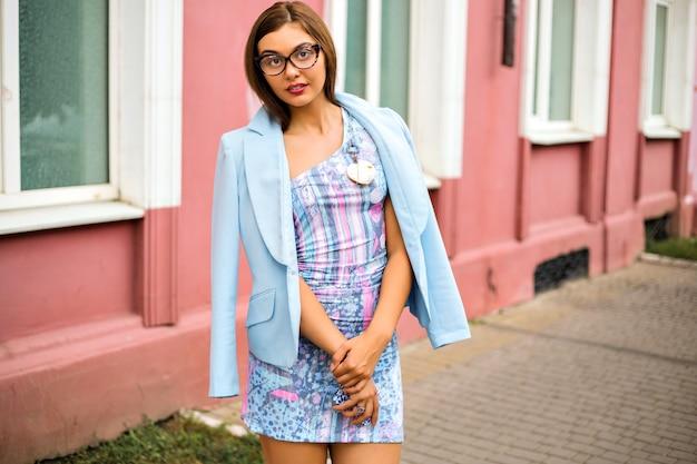 Moda na zewnątrz w stylu ulicznym wygląda na elegancką seksowną dziewczynę, ubrana w klasyczną mini sukienkę i błękitną kurtkę