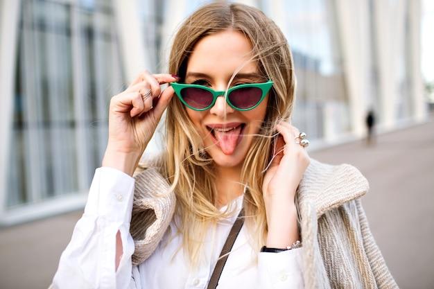Moda na zewnątrz z bliska portret pięknej blond kobiety biznesu, uśmiechnięta i patrząc na kamerę, kaszmirowy płaszcz, okulary przeciwsłoneczne w stylu vintage, biżuteria, delikatne kolory.