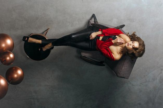 Moda pełnej długości portret wspaniały model w modnej odzieży. kobieta patrzy na swoje odbicie w lustrzanym suficie