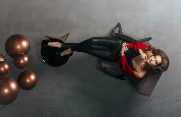 Moda pełnej długości strzał sexy model w modnej odzieży. kobieta patrzy na swoje odbicie w lustrzanym suficie