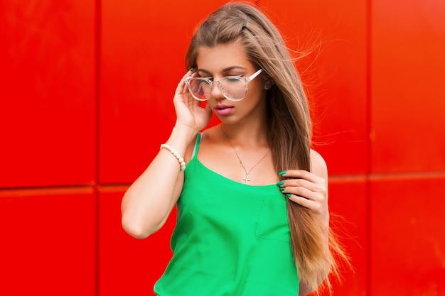 Moda piękna dziewczyna w stylowych okularach i jasne letnie ubrania w pobliżu czerwonej ściany