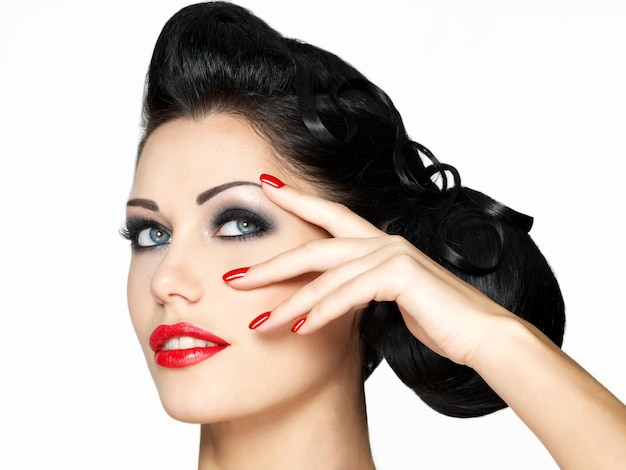 Moda piękna dziewczyna z czerwonymi ustami i paznokciami - na białym tle na białej ścianie