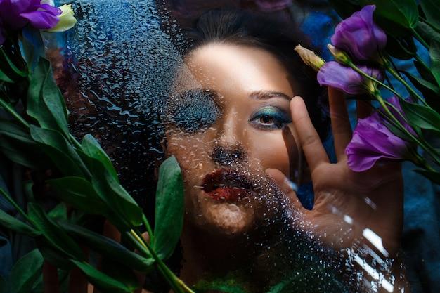 Moda piękna dziewczyna z jasnym makijażem wśród eustom.