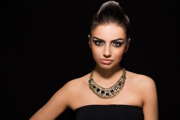Moda. piękna kobieta pozuje w czerni sukni