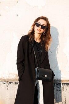 Moda piękna kobieta w czarnej odzieży wierzchniej na ulicy