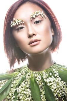 Moda piękna orientalna dziewczyna z delikatnym naturalnym makijażem i kwiatami.