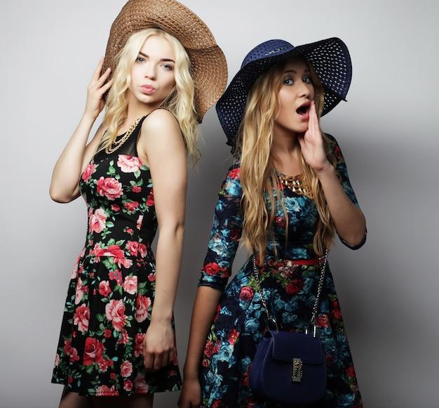 Moda piękny portret dwóch stylowych seksownych dziewczyn najlepszych przyjaciół, ubranych w sukienkę i kapelusze. szczęśliwy czas na zabawę.