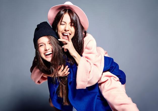 Moda piękny portret dwóch uśmiechniętych kobiet brunetka modelki w lato dorywczo hipster płaszcz pozowanie. dziewczyny trzymające się na plecach