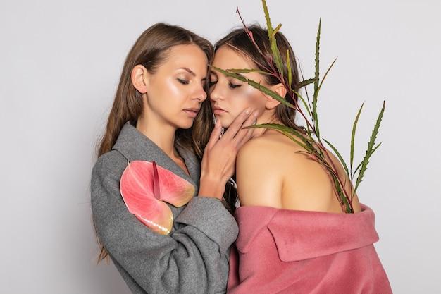 Moda piękny portret dwóch uśmiechniętych modeli brunetka kobiet w letni płaszcz dorywczo hipster pozowanie na szarym tle. pełna długość. format panoramiczny 16:9.