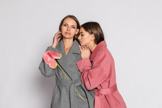 Moda piękny portret dwóch uśmiechniętych modeli brunetka kobiet w letni płaszcz dorywczo hipster pozowanie na szarym tle. pełna długość.