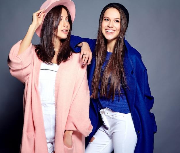 Moda piękny portret dwóch uśmiechniętych modeli kobiet brunetka w lecie dorywczo hipster płaszcz pozowanie na szaro