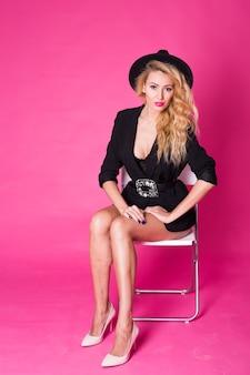 Moda piękny portret eleganckiej młodej kobiety z kręconymi blond włosami na różowej ścianie