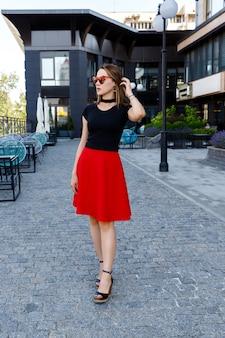 Moda piękny portret kobiety w czarnej koszulce i czerwonej spódnicy spaceru na ulicy. akcesoria do modnych ubrań i okularów. koncepcja sprzedaży zakupów