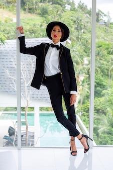Moda piękny portret kobiety w czarnym garniturze, krawacie motyla i kapeluszu w luksusowej willi