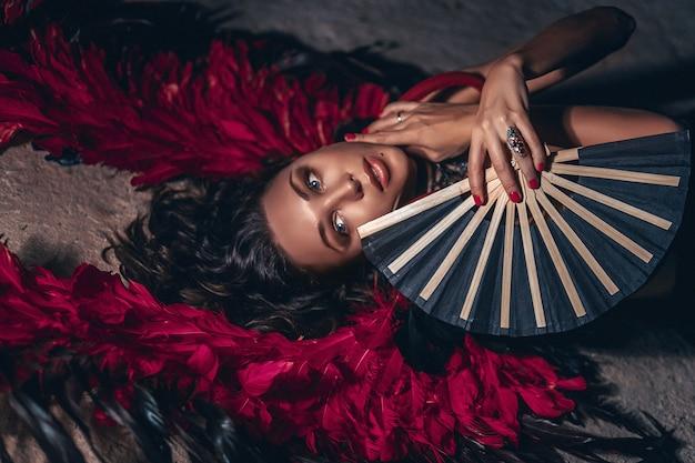 Moda piękny portret kobiety z pasją na sobie czarną sukienkę z czerwonymi anielskimi skrzydłami i czarnym fanem w ręku. moda ciemnego piękna.