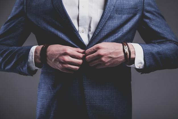 Moda piękny portret młodego biznesmena przystojny model mężczyzna ubrany w elegancki niebieski garnitur na szaro