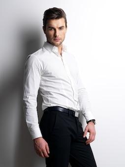 Moda piękny portret młodego mężczyzny w białej koszuli pozuje na ścianie z kontrastowymi cieniami