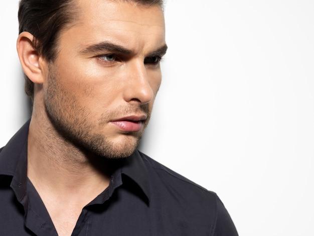 Moda piękny portret młodego mężczyzny w czarnej koszuli pozuje na ścianie z kontrastowymi cieniami