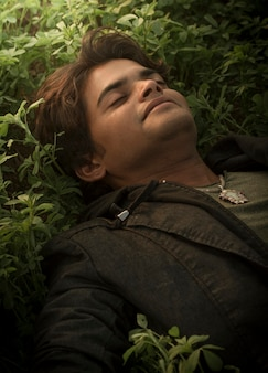 Moda piękny portret młodego mężczyzny w czarnej marynarce, leżeć na zielonej trawie