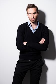 Moda piękny portret młodego mężczyzny w czarny sweter i niebieską koszulę ze skrzyżowanymi rękami