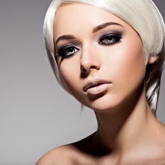 Moda piękny portret młodej kobiety o blond włosach i czarnym makijażu oczu
