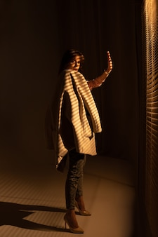 Moda piękny portret młodej kobiety, pozowanie w pokoju, na sobie szary płaszcz.