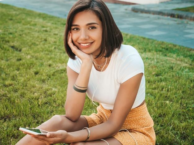 Moda piękny portret młodej kobiety stylowe hipster. dziewczyna sobie ładny modny strój. uśmiechający się model cieszyć się jej weekendy, siedząc w parku. kobieta słuchania muzyki przez słuchawki