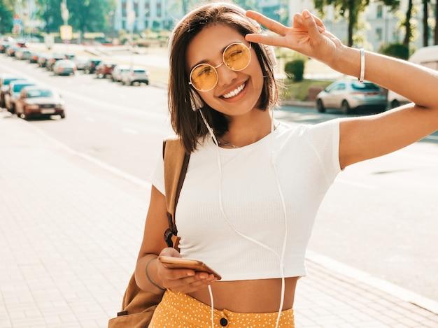 Moda piękny portret młodej kobiety stylowe hipster spaceru na ulicy. dziewczyna ubrana w ładny modny strój. uśmiechnięty model cieszyć się jej weekendy, podróż z plecakiem. kobieta słuchania muzyki przez słuchawki