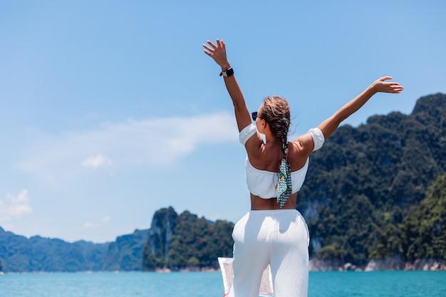 Moda piękny portret młodej kobiety w biały top i spodnie na wakacje, na żaglówce tajskiej drewnianej łodzi. koncepcja podróży. samica w parku narodowym khao sok.