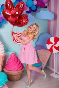 Moda piękny portret młodej kobiety w różowej sukience z balonów, cukierki na kolorowy