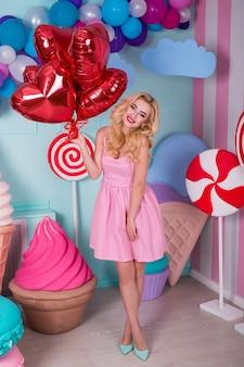 Moda piękny portret młodej kobiety w różowej sukience z balonów, cukierki na kolorowym tle.