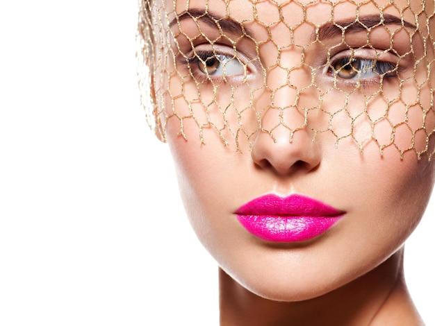 Moda piękny portret pięknej dziewczyny nosi zasłonę na oczach. jasny makijaż. na białym tle na białej ścianie
