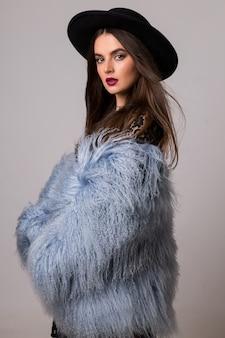 Moda piękny portret pięknej kobiety w stylowy zimowy puszysty niebieski płaszcz i czarny kapelusz pozowanie na jasnoszarej ścianie.