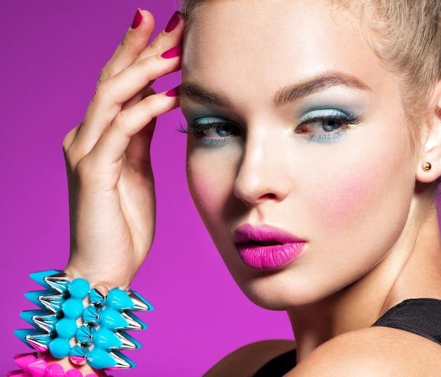 Moda piękny portret pięknej kobiety z jasnym makijażem zbliżenie twarzy pięknej modelki wspaniała twarz atrakcyjnej dziewczyny różowa ściana portret dziewczyny z bransoletki ciernie