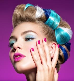 Moda piękny portret pięknej kobiety z niebieskim makijażem i różowymi paznokciami. piękna modelka. wspaniała twarz atrakcyjnej dziewczyny - różowe tło.