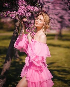 Moda piękny portret pięknej młodej kobiety o blond włosach w wiosennym różowym kwitnącym ogrodzie w długiej różowej sukience niczym księżniczka z bajki