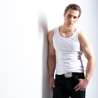 Moda piękny portret seksownego młodzieńca w białej koszuli pozuje na ścianie z kontrastowymi cieniami.