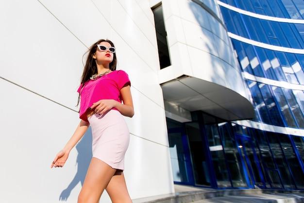 Moda piękny portret seksowny jasny seksowna kobieta w różowej bluzce i spódnicy z doskonałymi długimi nogami chodzenia na nowoczesnym tle miejskim.