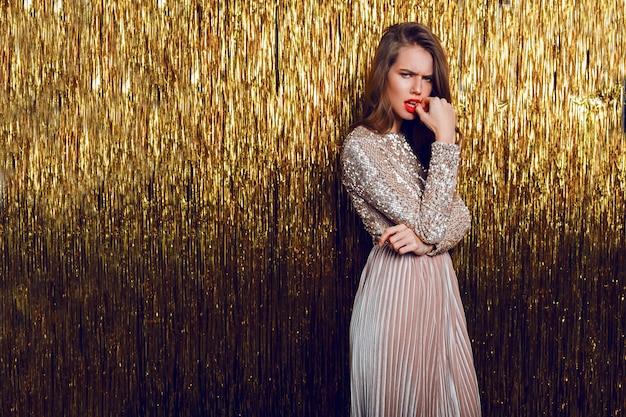 Moda piękny portret zmarszczonej brwi kobiety stojącej nad złotym musujące