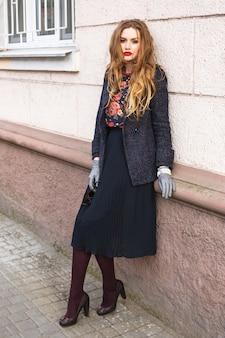 Moda plenerowa portret pięknej stylowej dziewczyny pozującej na ulicy w eleganckim, stylowym płaszczu i czółenkach, ma długie rude włosy i idealnie dopasowane akcesoria.