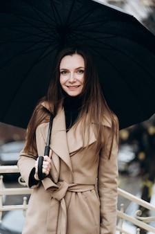 Moda plenerowa portret stylowej młodej kobiety bawiącej się, budzącej emocje twarzy, śmiejącej się, miejskiego stylu ulicy w ciemnych spodniach, białym swetrze, kremowym płaszczu i okularach przeciwsłonecznych. koncepcja mody.